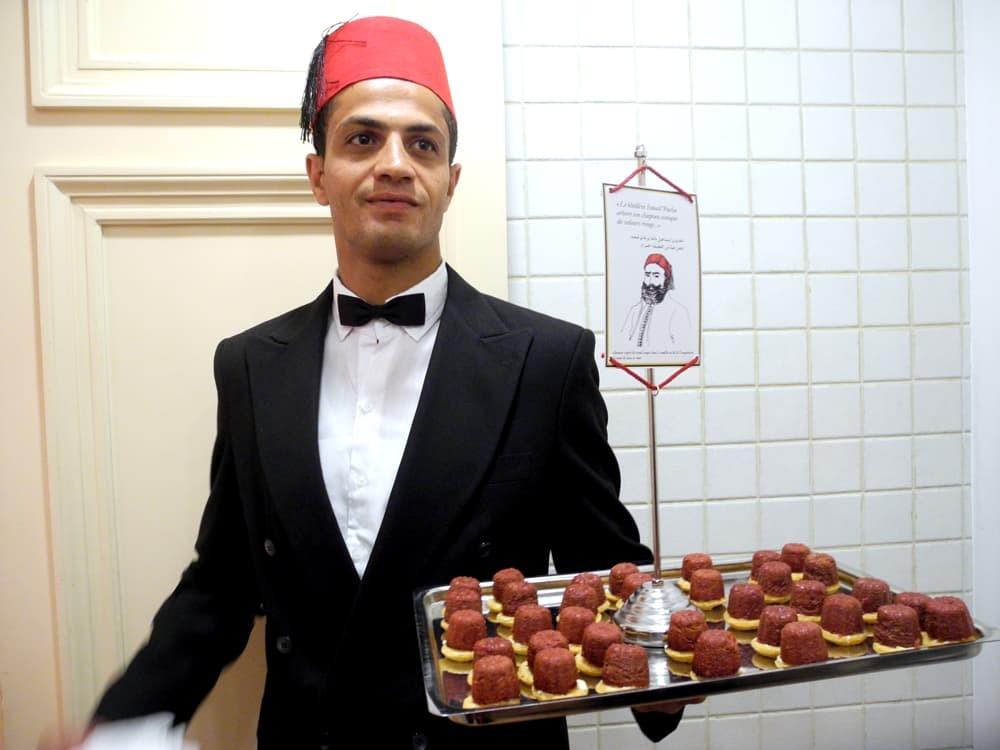 Plateau et serveur. Bouchée rouge inspirée de la forme du chapeau du khédive Ismaïl Pacha.